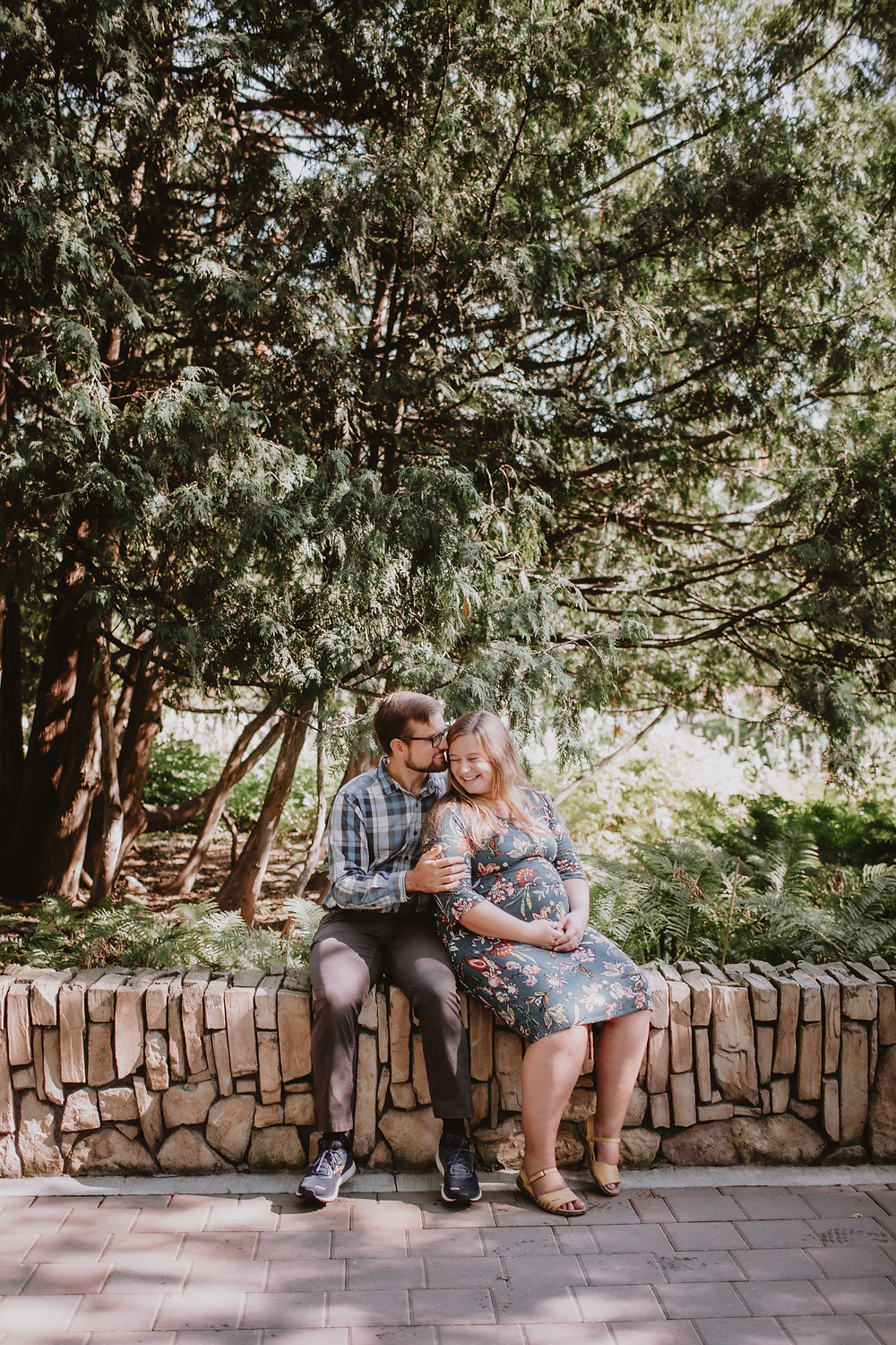 Couple sits by the English Gardens during maternity photo shoot.