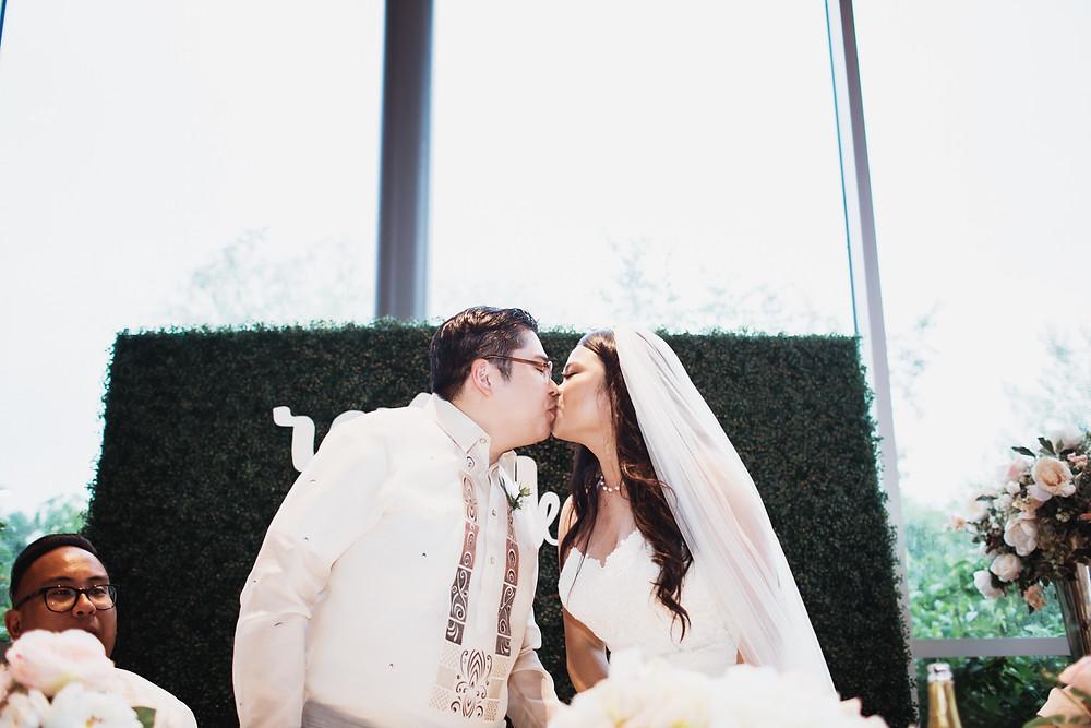 Winnipeg wedding couple share a kiss during their reception in Assiniboine Park.