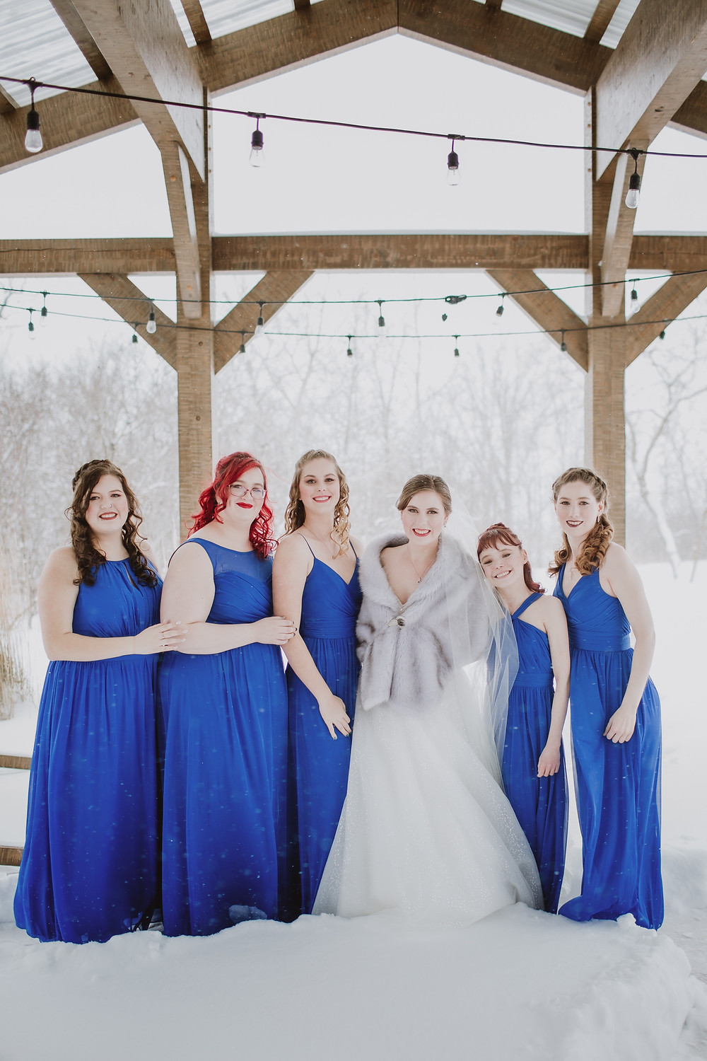 Bridesmaid in royal blue dreses for winter wedding day.