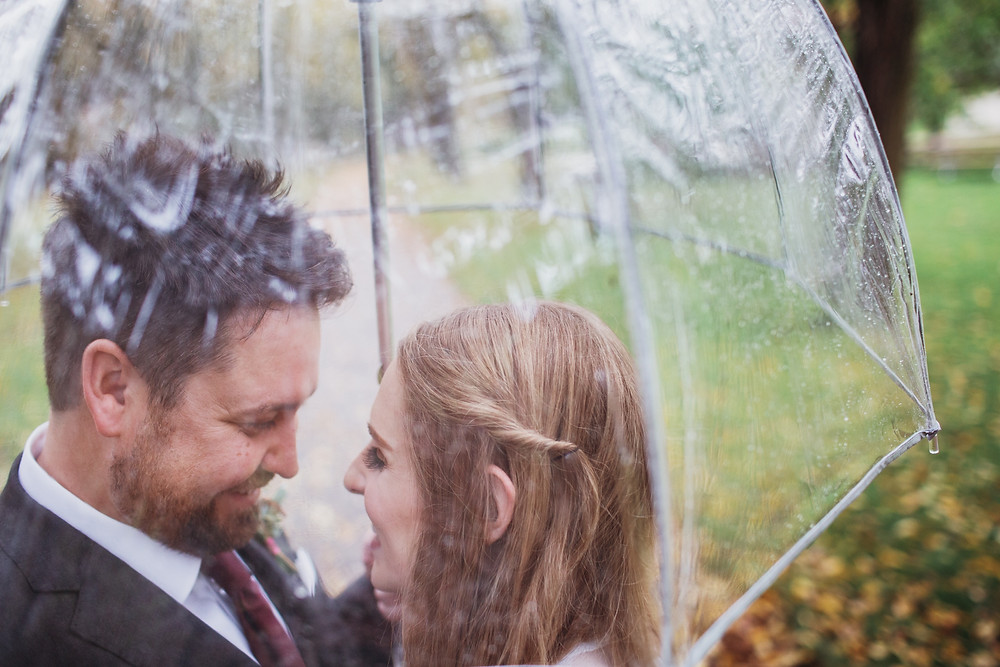 Wedding couple under a clear umbrella in Clear Lake, Manitoba.