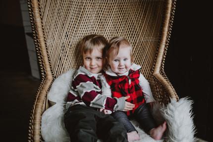 Siblings Cuddle on Wicker Chair