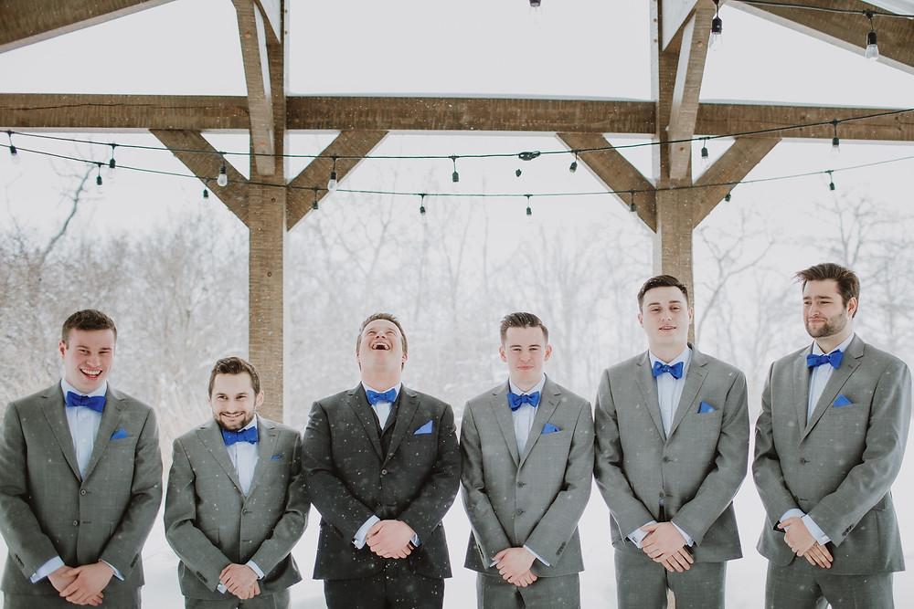 Groom in dark grey suit and groomsmen in grey suits from Moore's.