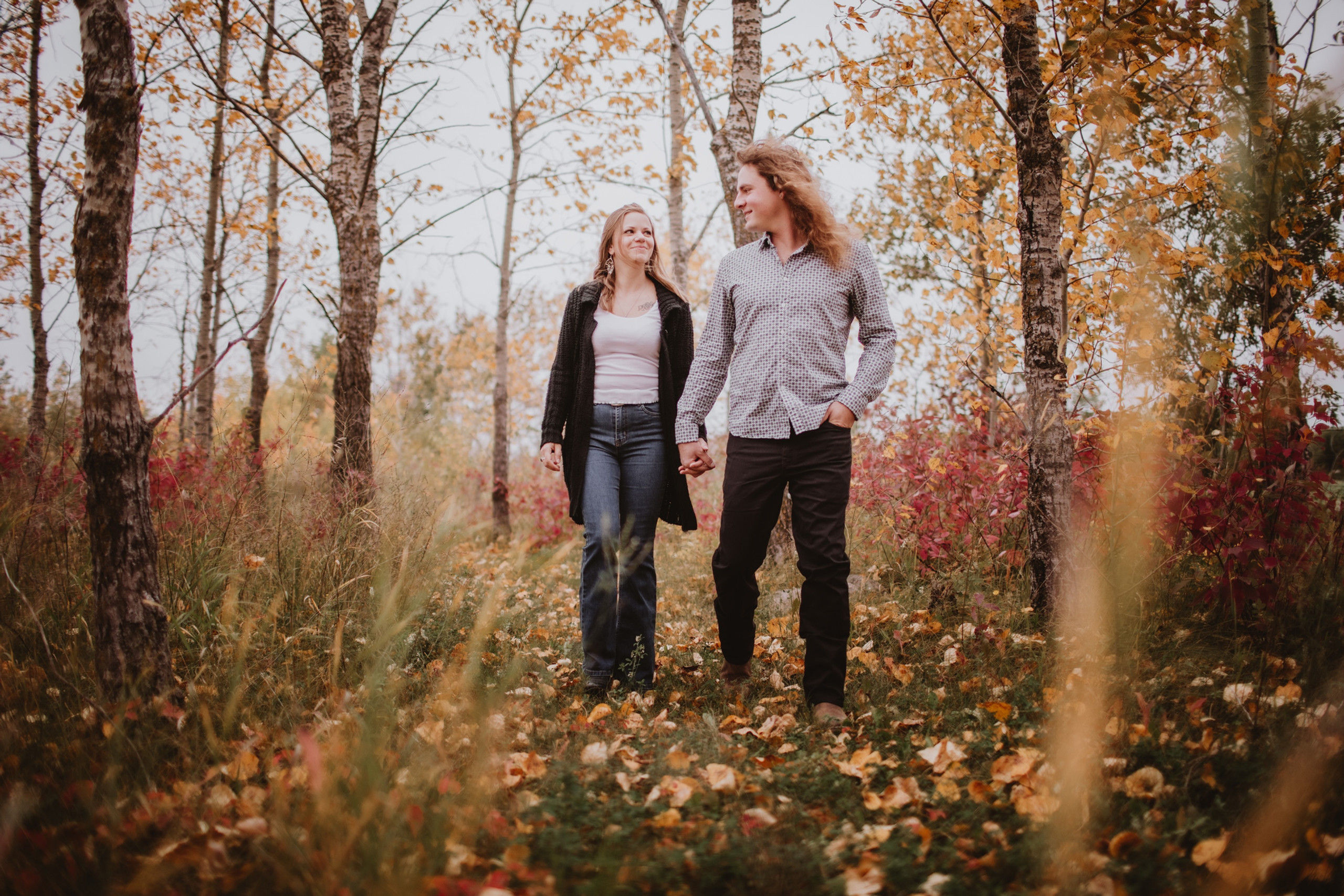 Couple Walks Through Forest in the fall, in Manitoba.