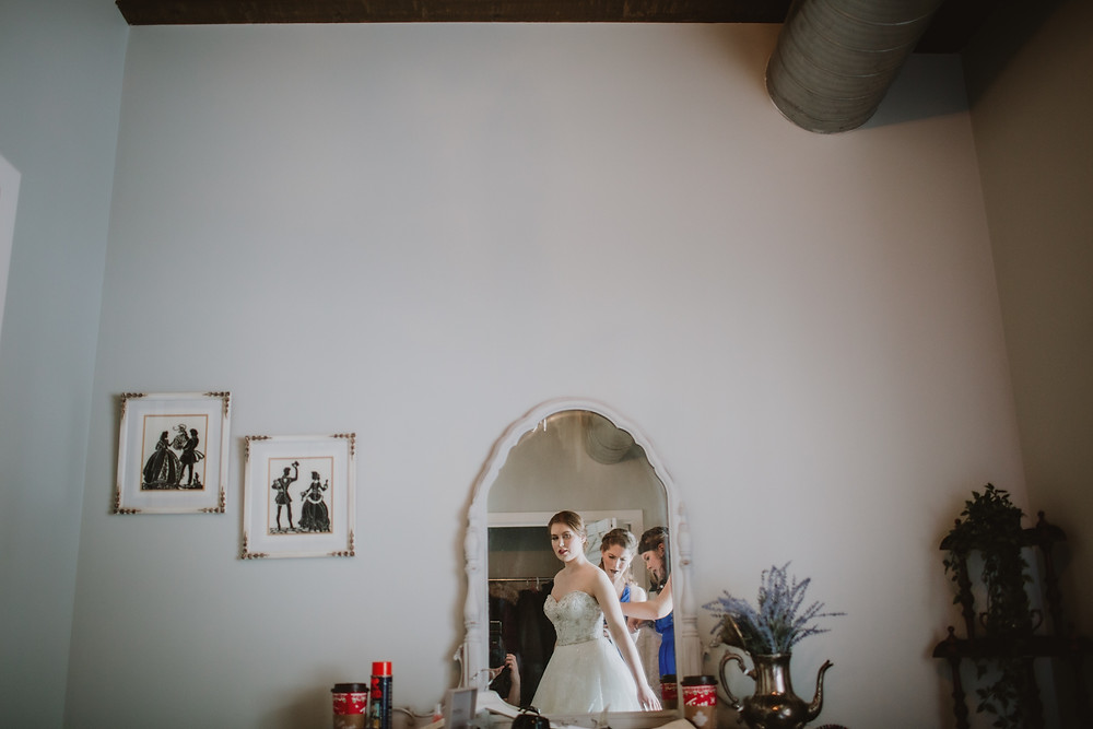 Bride getting ready to walk down the aisle, seen in the mirror of this bridal suite.