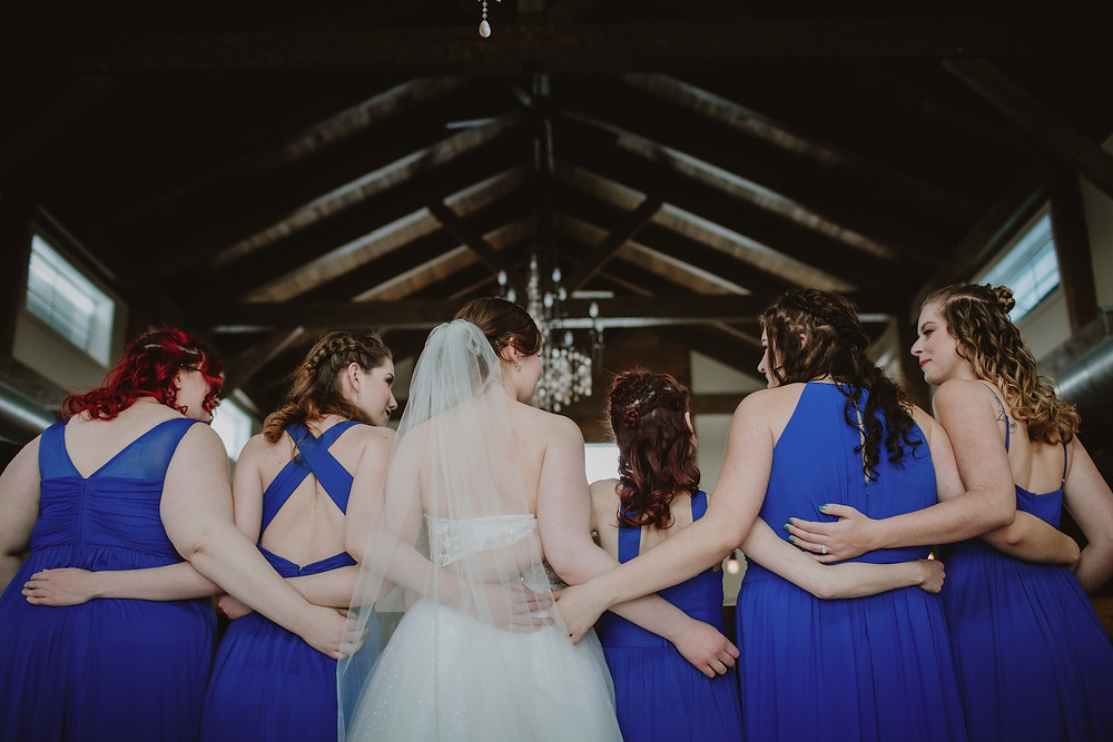 Bridesmaid portrait showcasing backs of royal blue gowns.