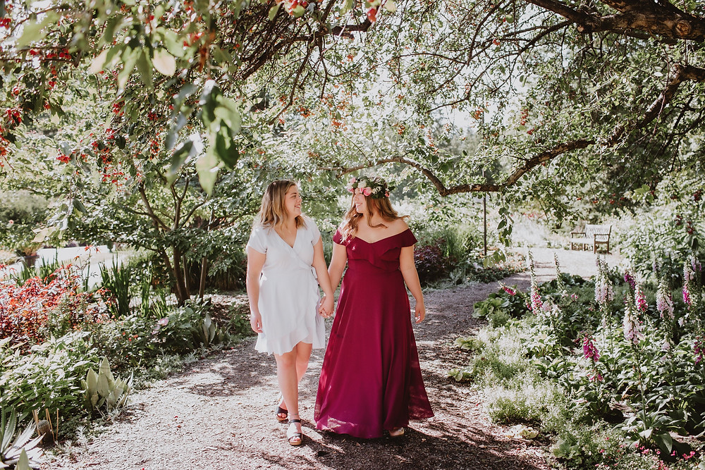 Sisters walk hand in hand through garden during grad portrait session.