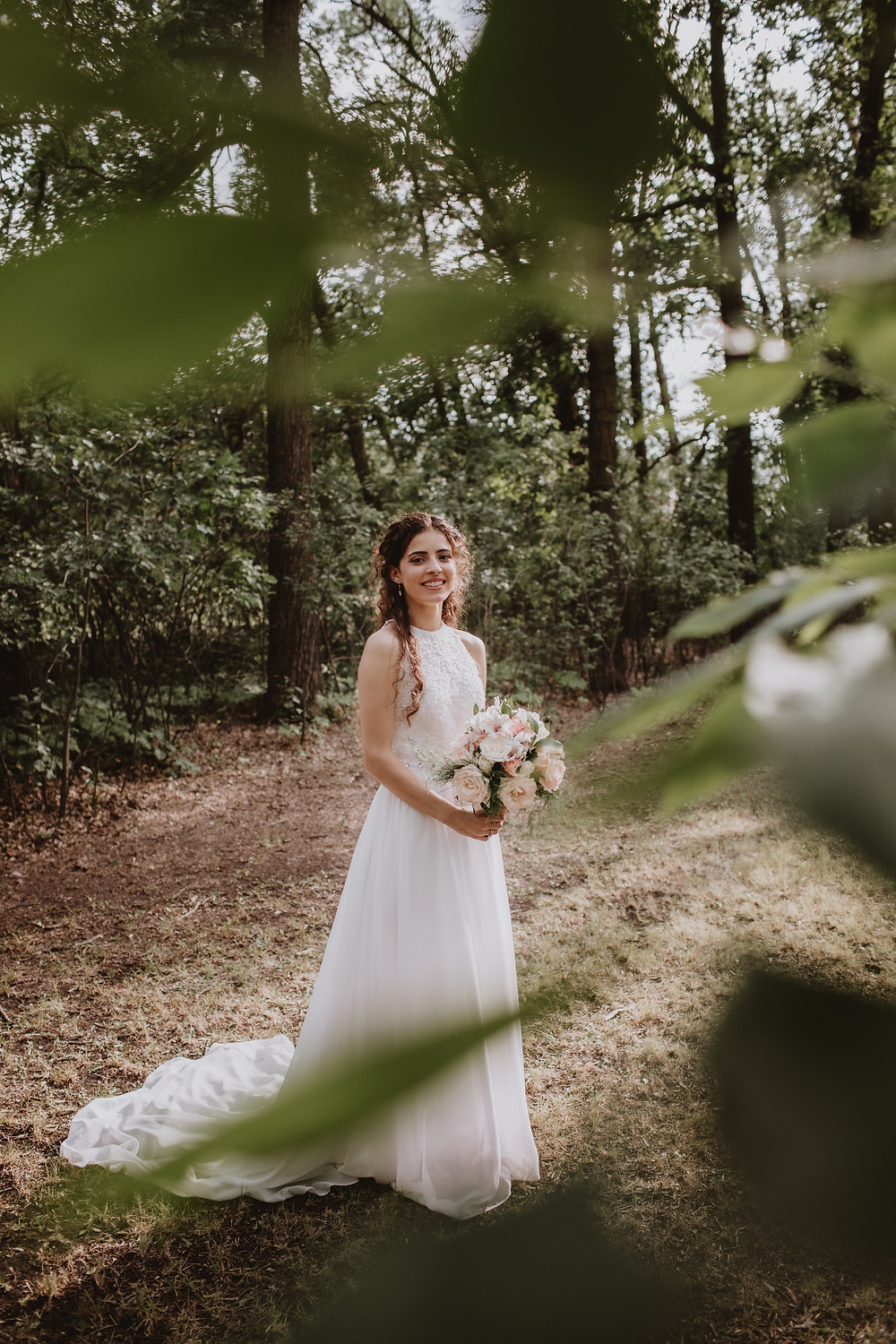 Smiling bride, posing in the forest for wedding portraits.