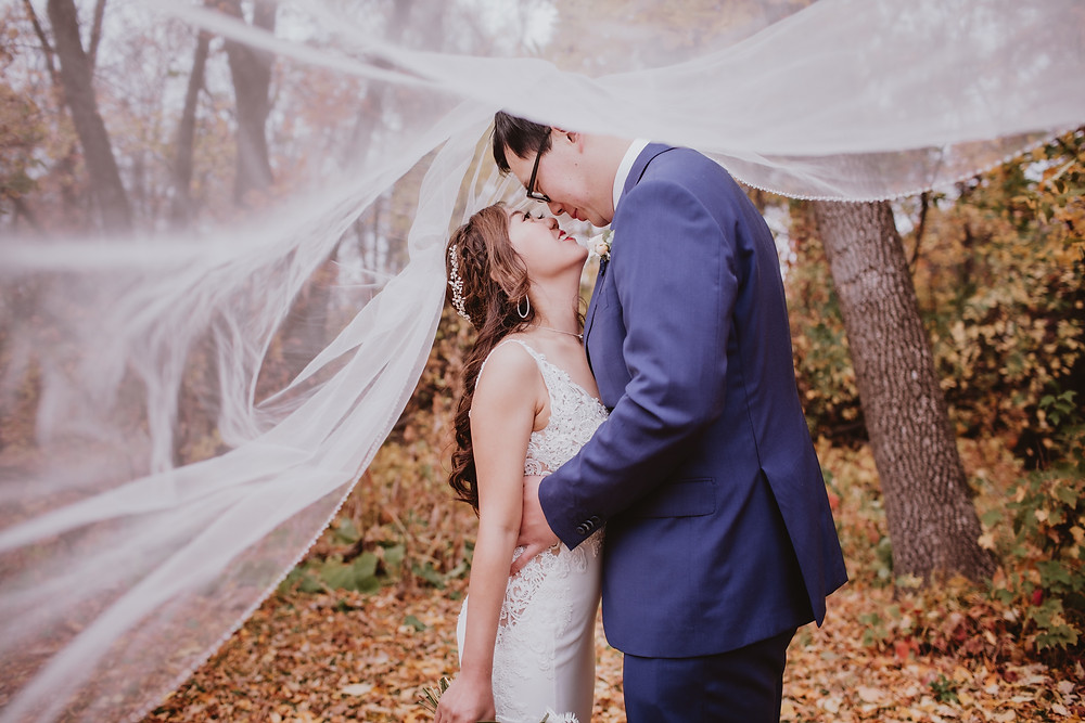 Bride and groom touch noses under veil for fall wedding in Manitoba.