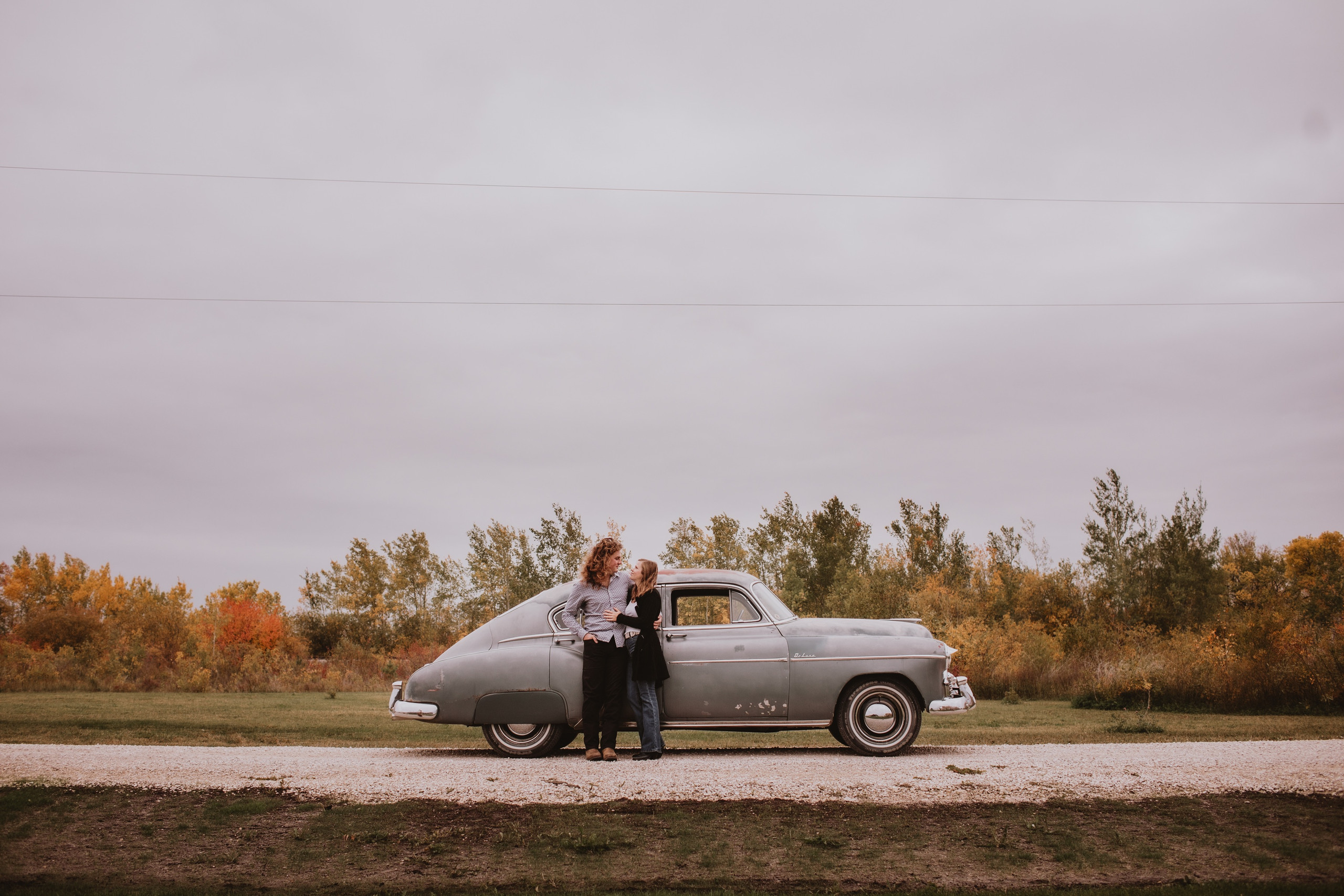 Couple Poses by Vintage Car during fall photoshoot in Manitoba.
