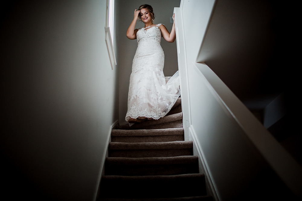 Bride walks down stairs before Winnipeg, fall wedding ceremony.