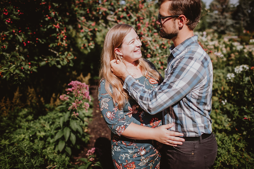 Couple poses in garden for maternity photos.