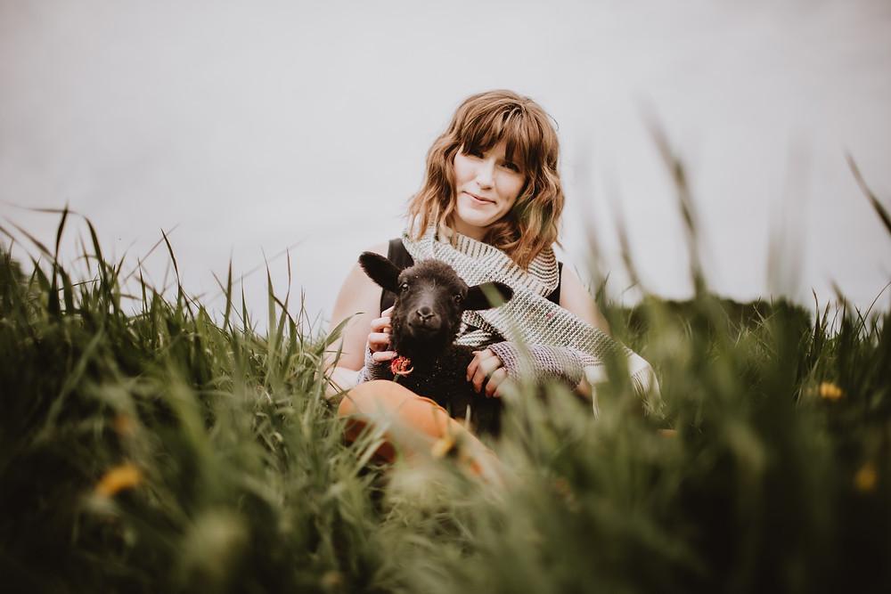 Fibre artist poses with lamb.