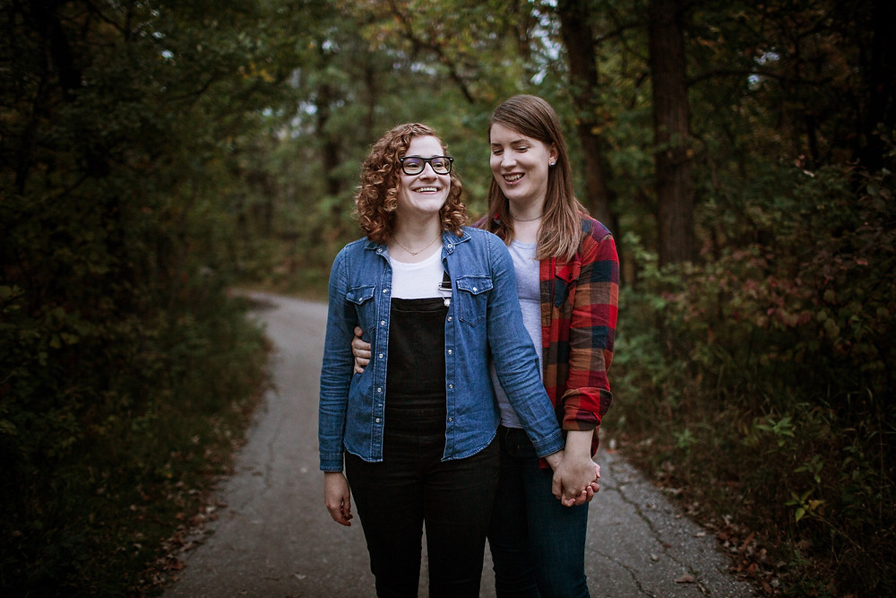 Same-sex poses in the forest for their engagement photos.