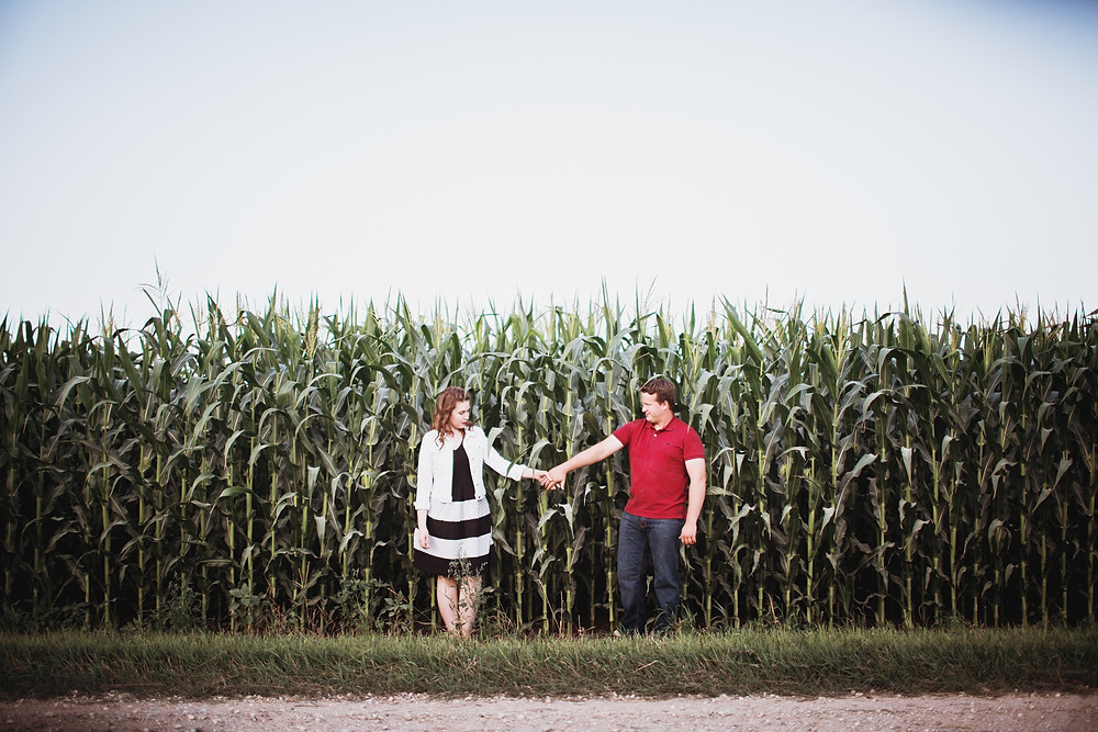Couple poses in their corn field during engagement photos.