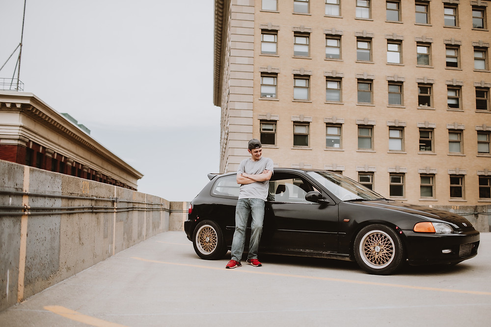 Graduate poses in front of black car.
