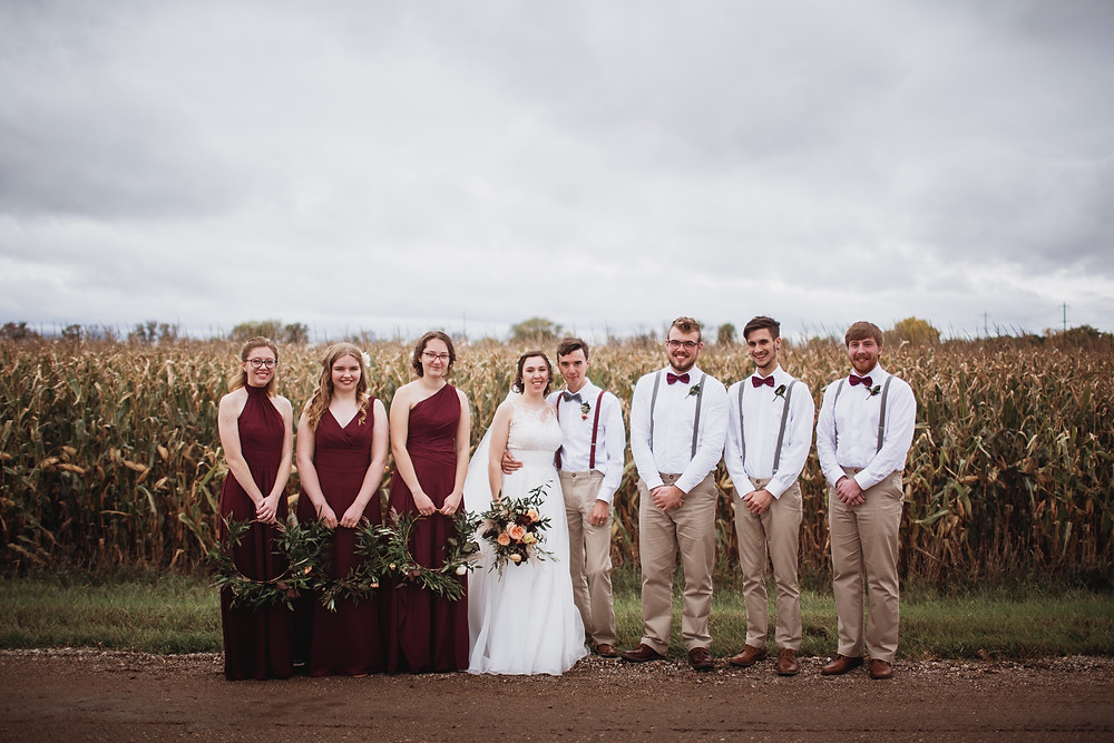 Fall bridal party poses infront of corn field.