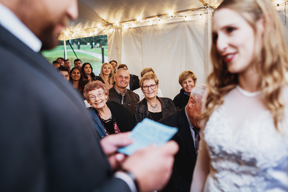 Bride's grandma intently watches bride exchange vows in her fall Manitoba wedding.