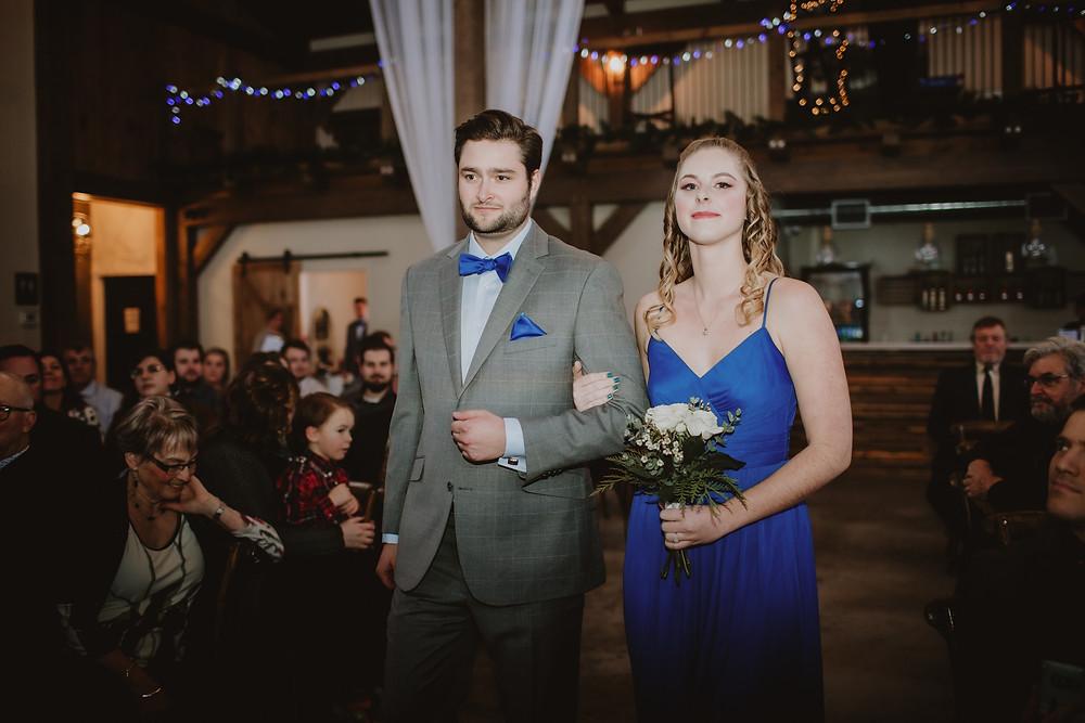 Bridesmaid and groomsman walk down aisle arm in arm.