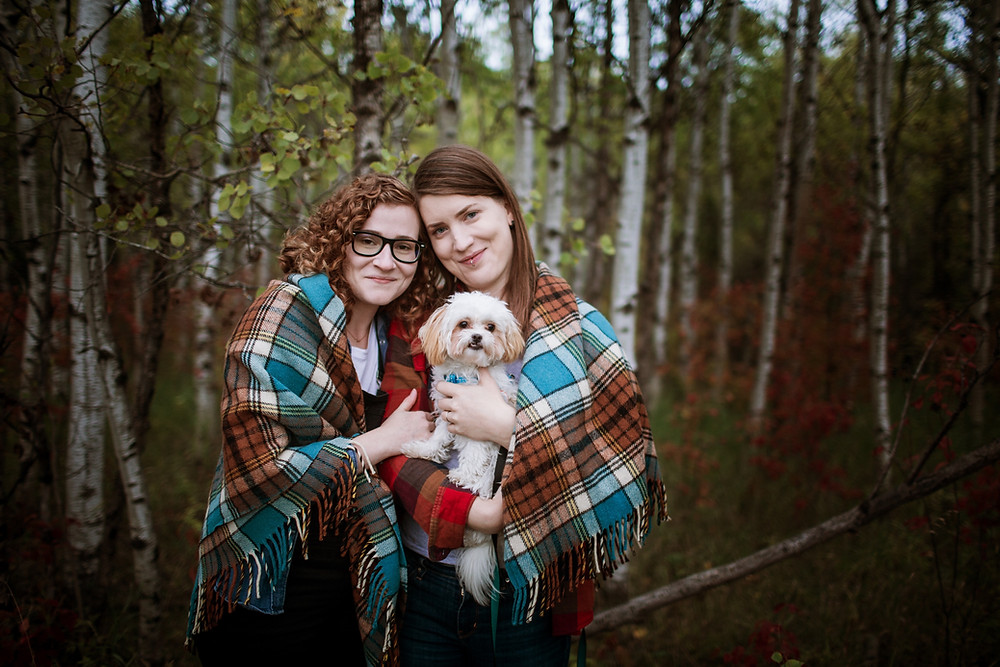 Dog-moms cuddle their tiny dog during their engagement photo session.