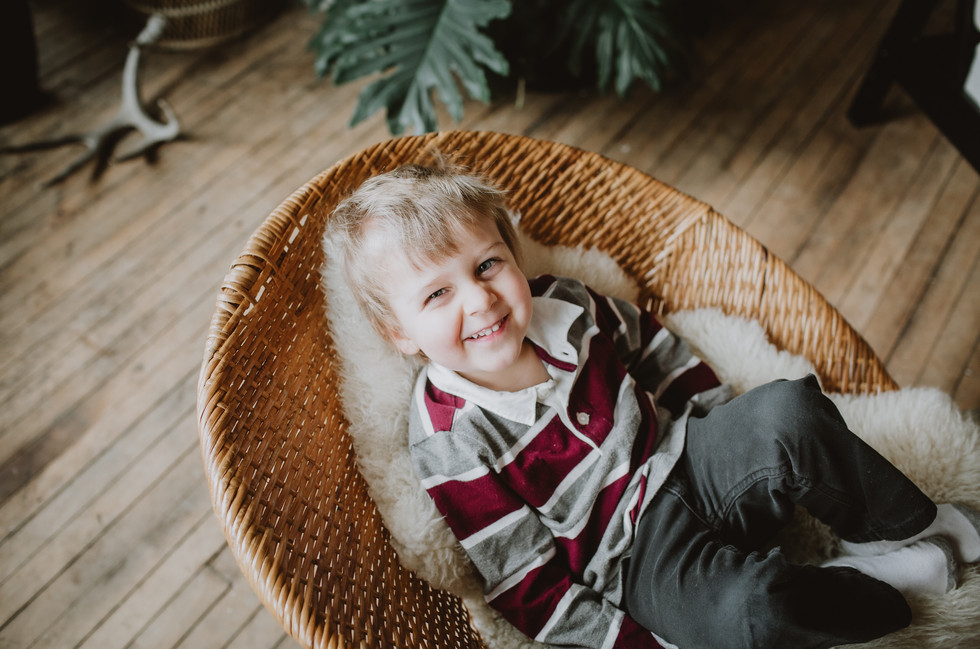 Boy Sits, Smiling on Wicker Bowl Chair