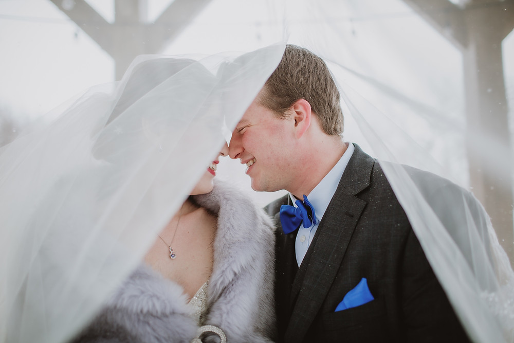 Wedding couple cuddles under veil for snowy wedding day portraits.