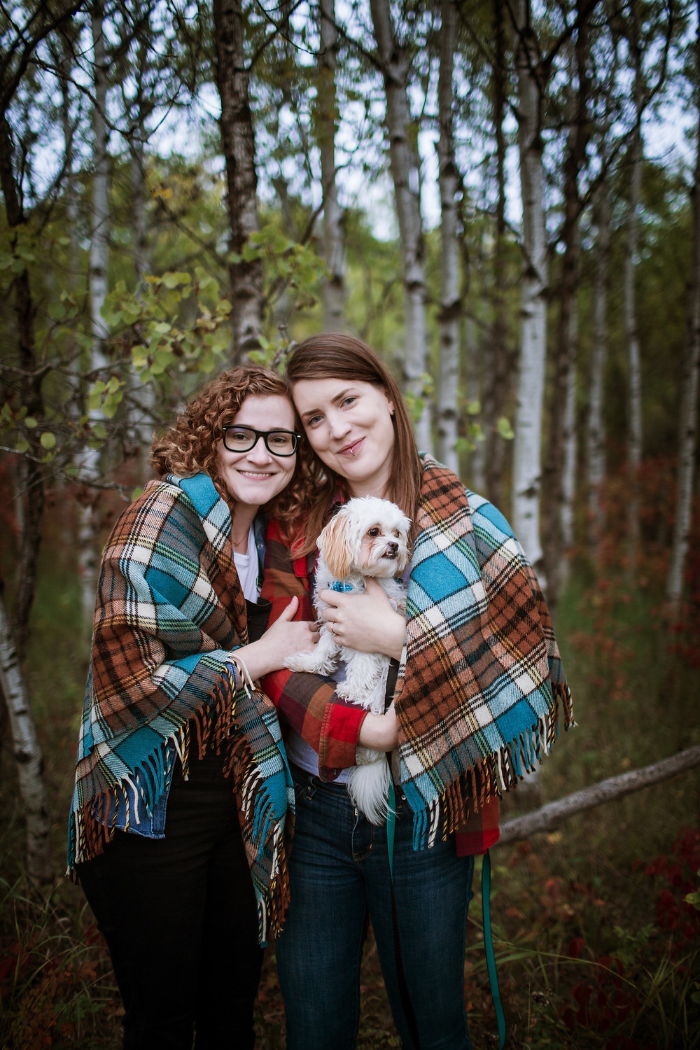 Couple cuddles their puppy during engagement photo session.