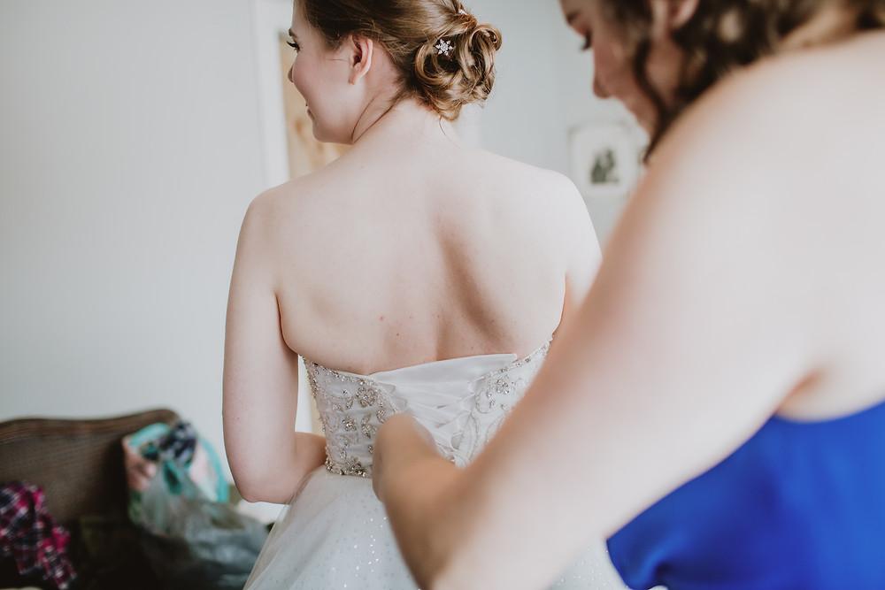 Bridesmaid closes brides corset.