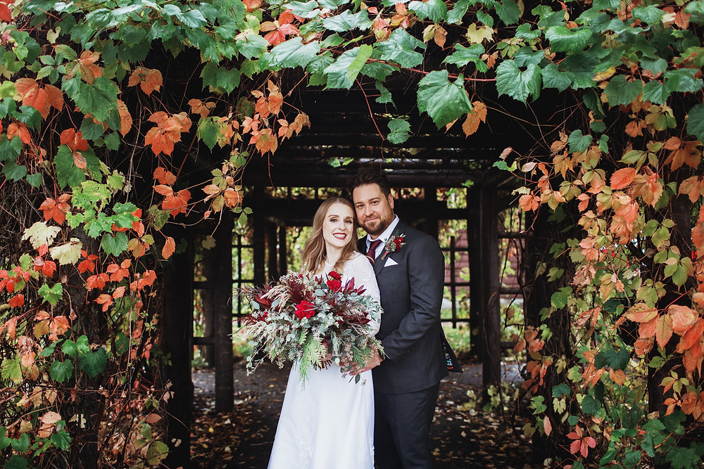 Portrait of a bride and groom, under green and orange ivy in Clear Lake, Manitoba.