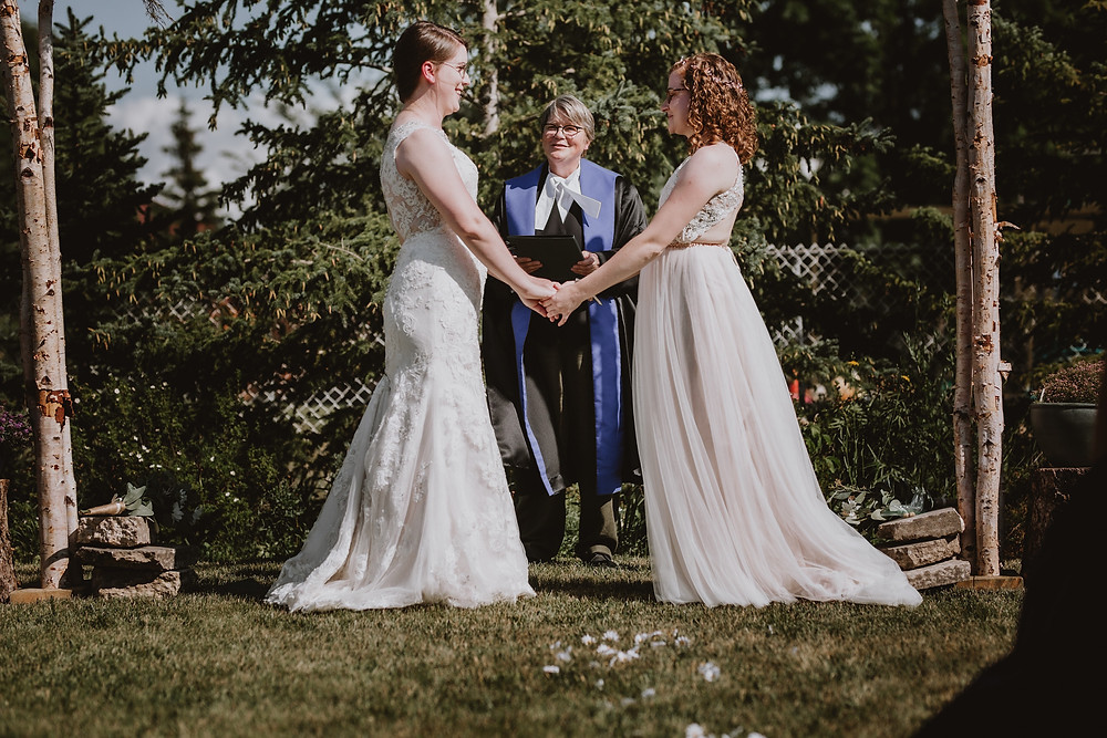Brides smile at each other during micro-wedding.