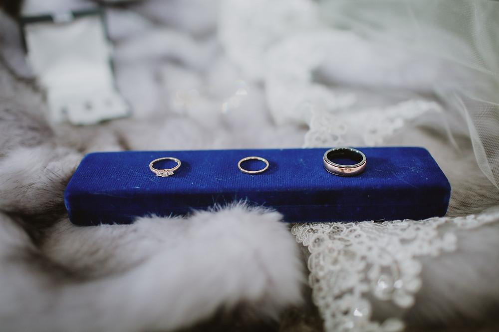 Wedding rings and engagement rings on velvet blue box.
