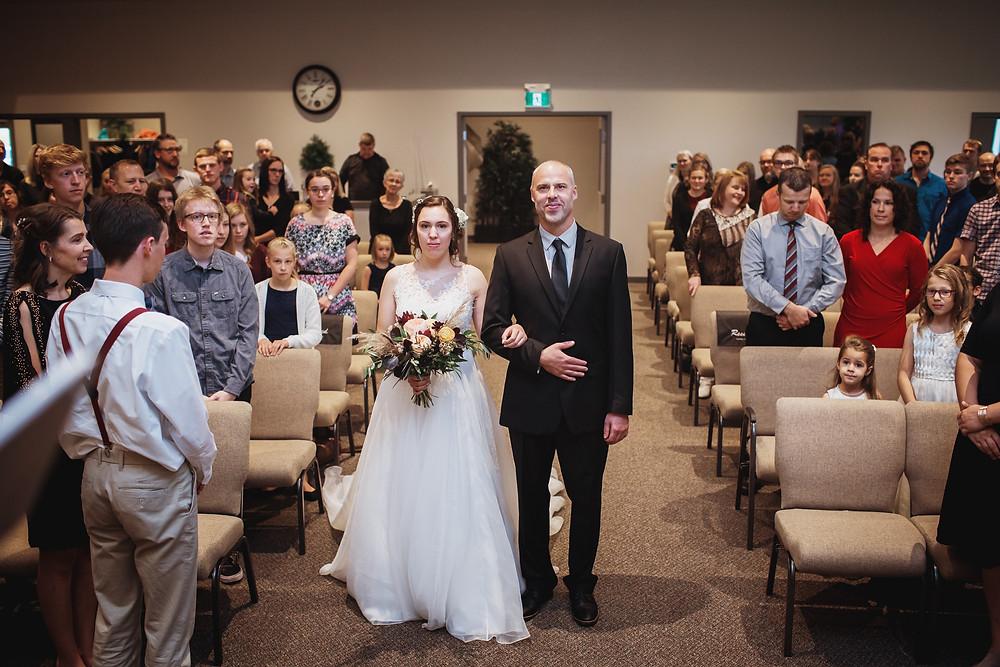 Father walks bride down aisle in church ceremony