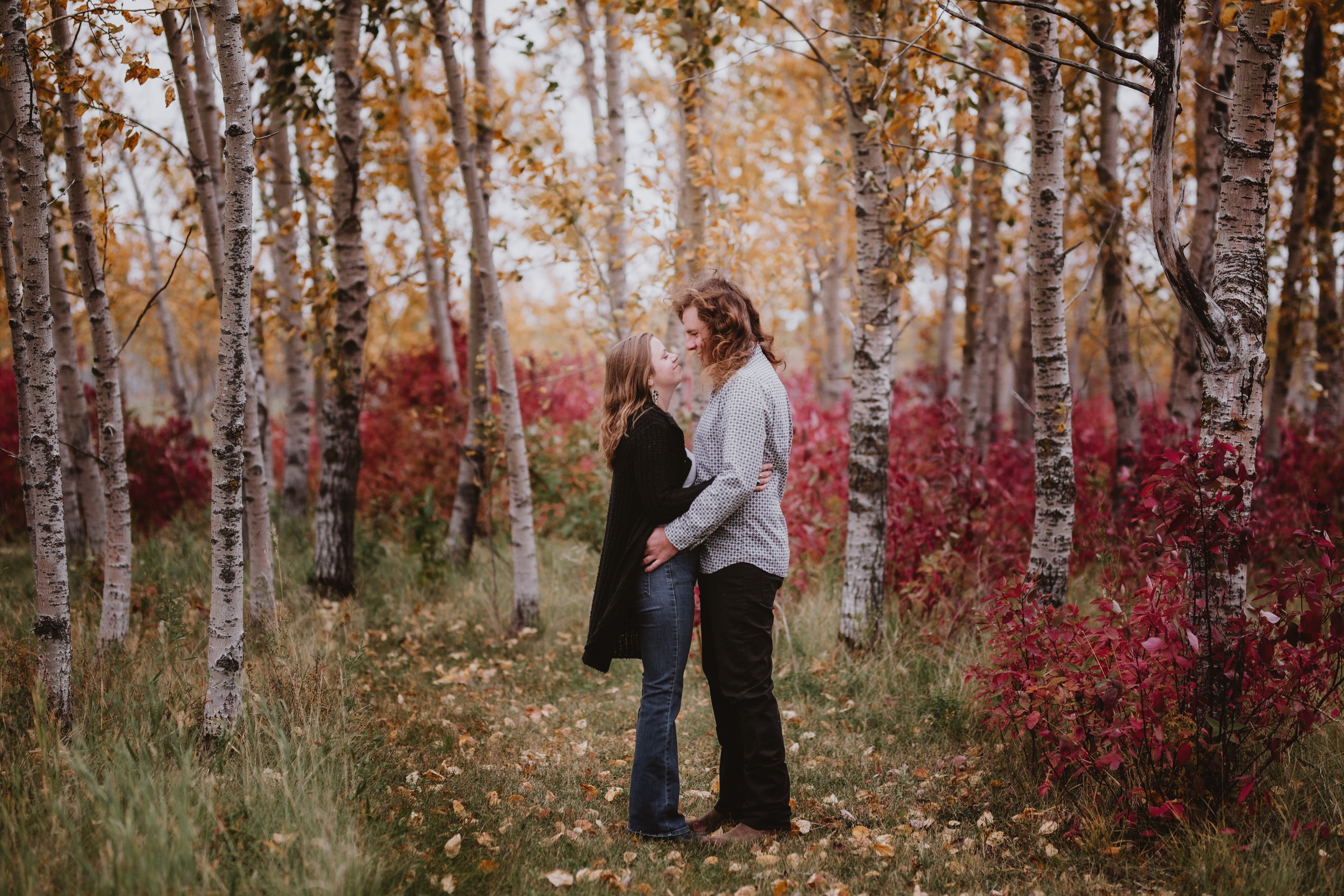 Couple Poses Amongst Trees during fall photoshoot.