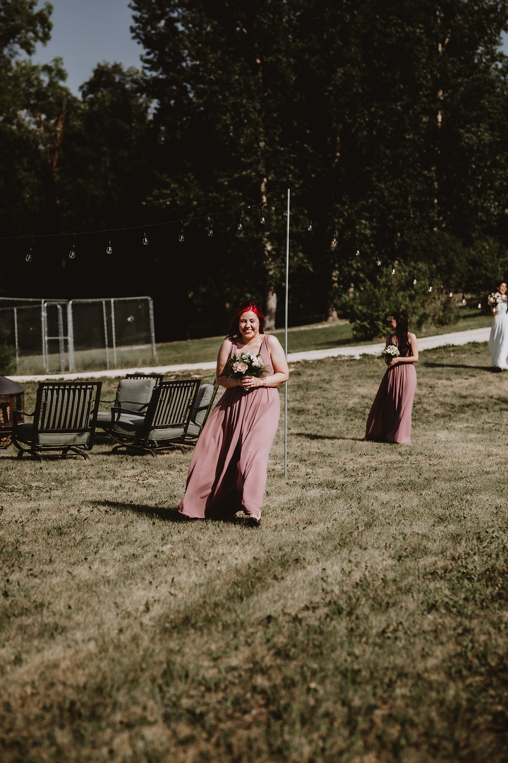 Smiling bridesmaid walking down the aisle during backyard wedding.