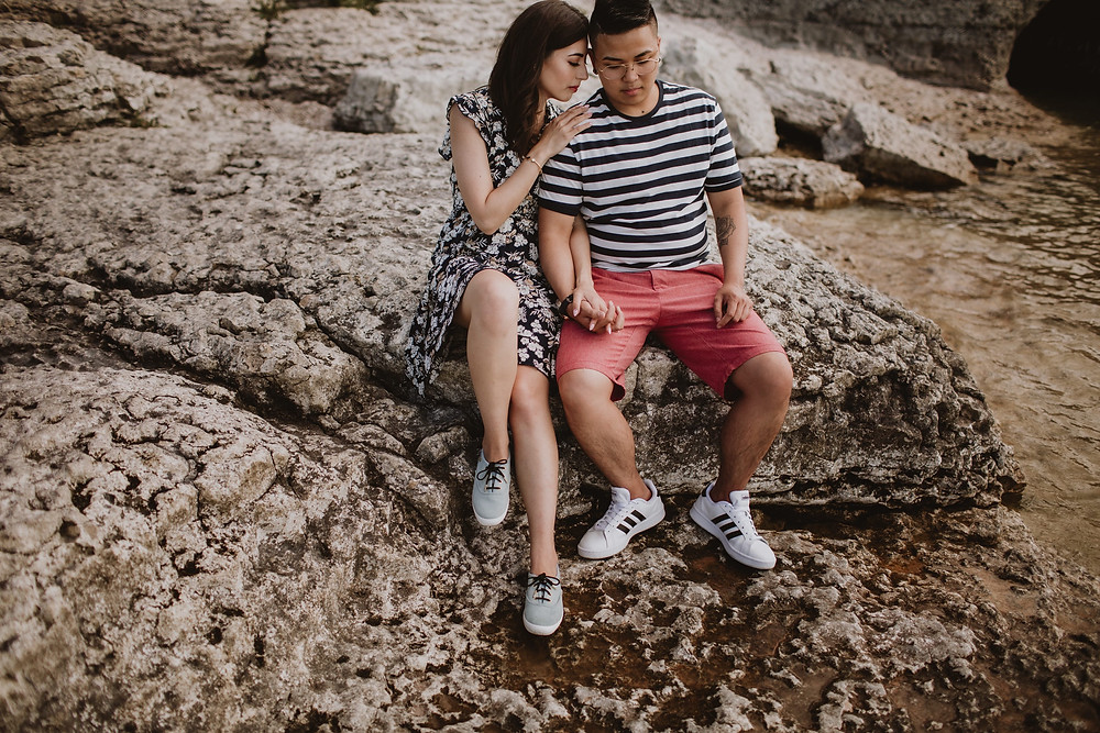 Couple poses on rocks, on the beach of Steep Rock, Manitoba