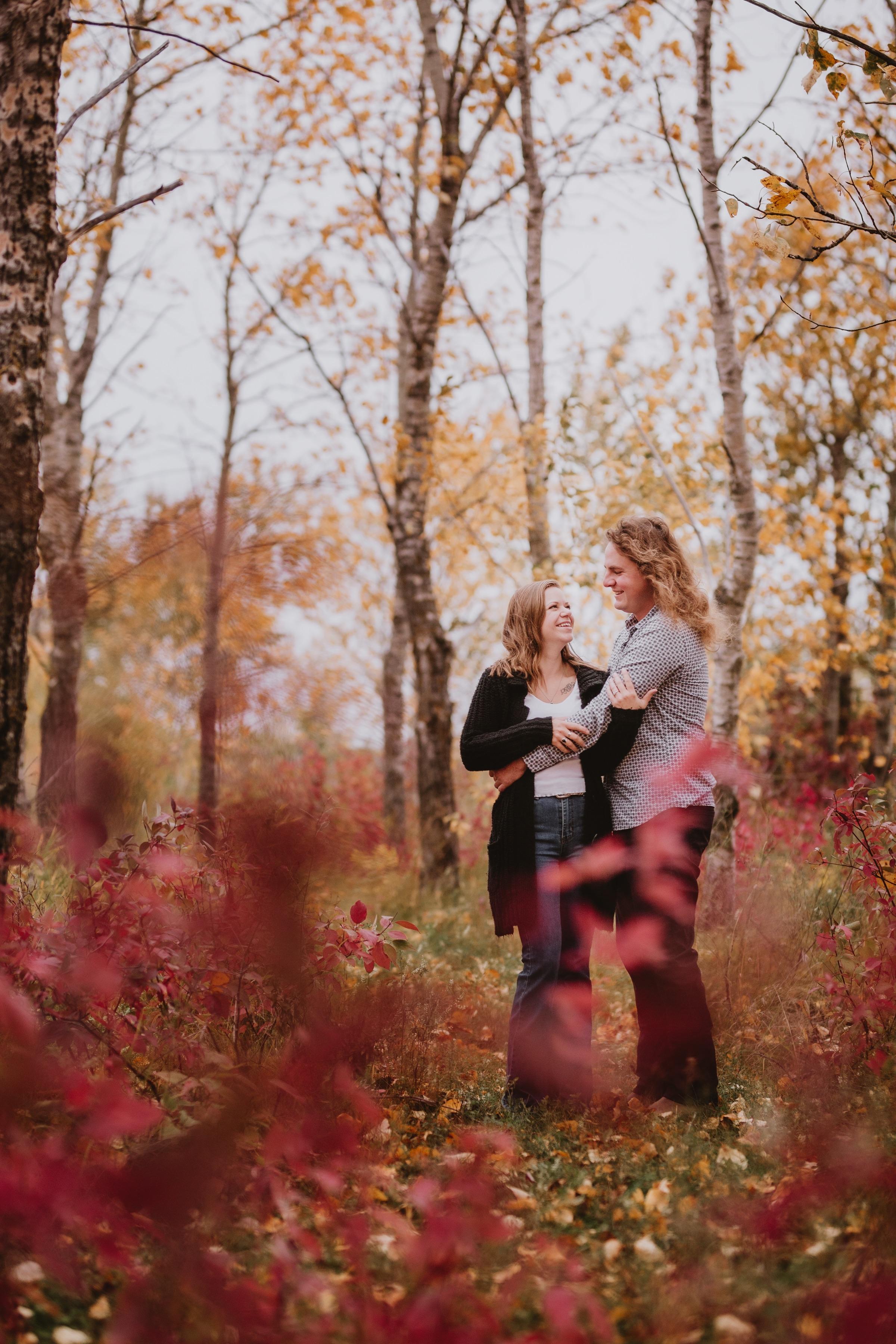 Engaged couple cuddles during fall engagement photoshoot.