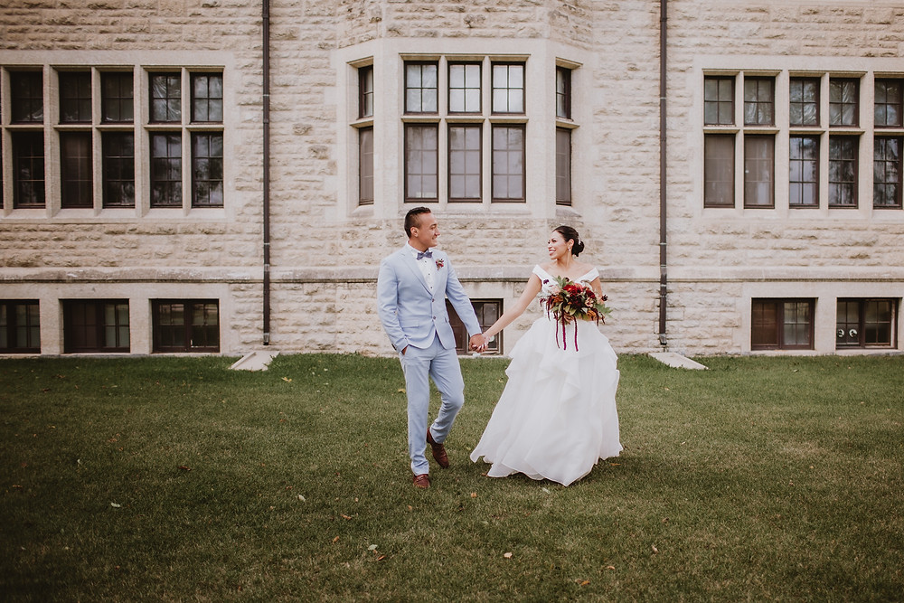 Bride and groom walk hand-in-hand away from beautiful building at CMU.