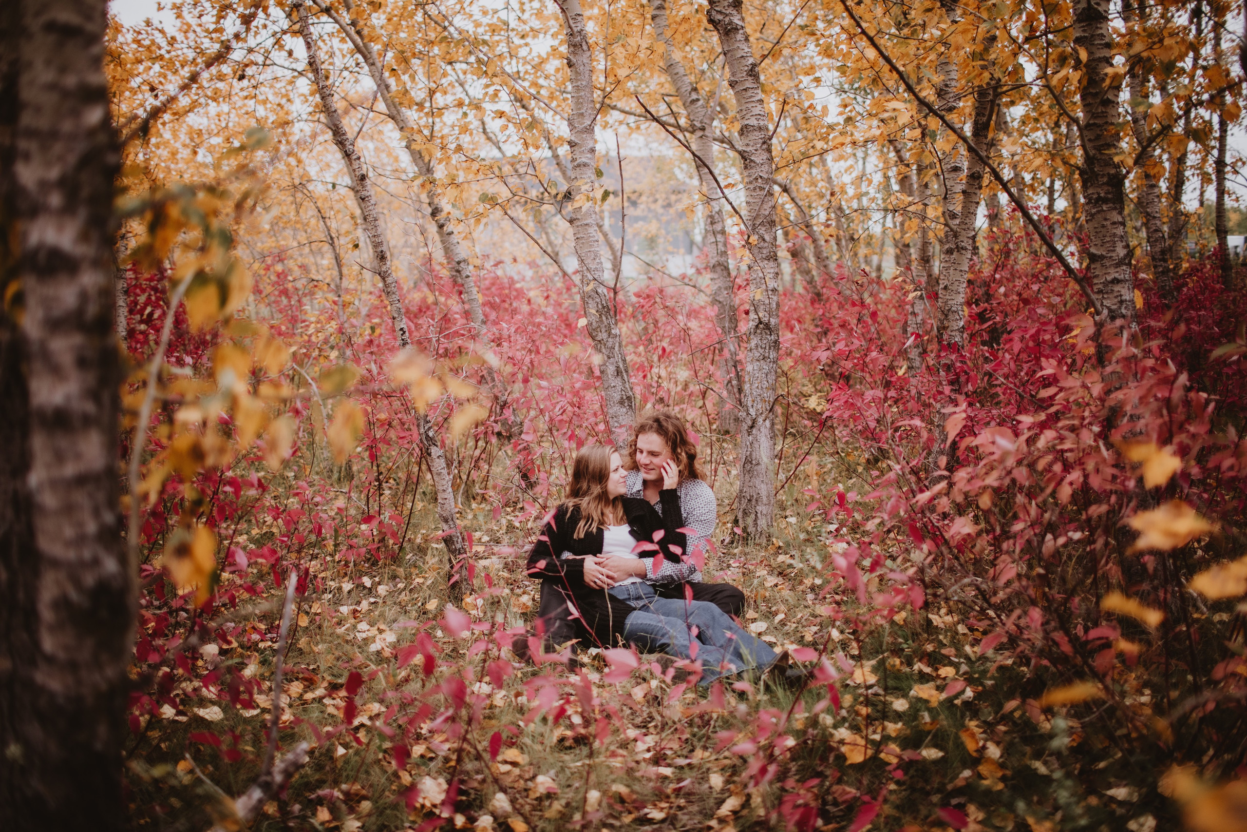 Couple Sitting in Forest during fall engagement session.