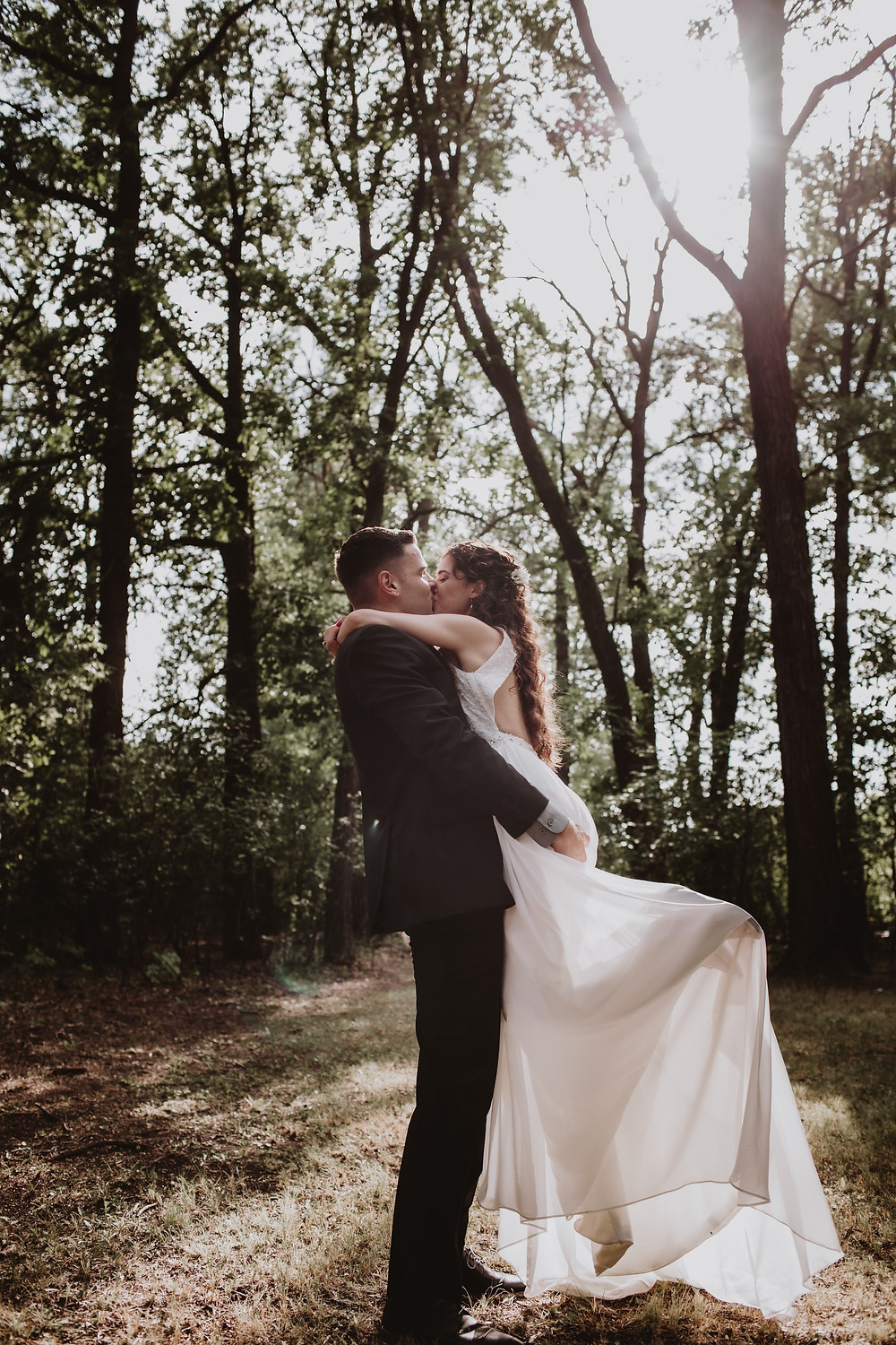Groom lifts and kisses bride inthe forest, in Winnipeg, Manitoba.