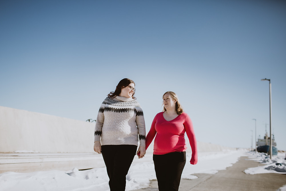 Same-sex couple walks hand-in hand along pier in Gimli, Manitoba.