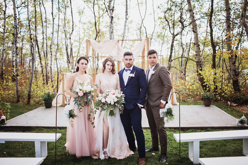 Bridal party in ceremony space, blush gowns with navy and neutral suits.