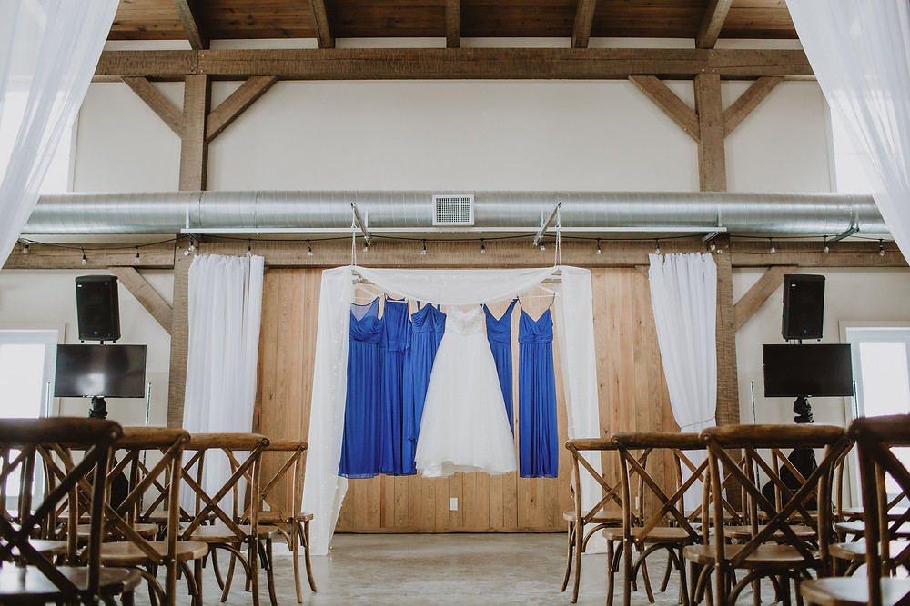 Wedding gown and bridesmaid gowns hang in ceremony space at Hawthorne Estates.