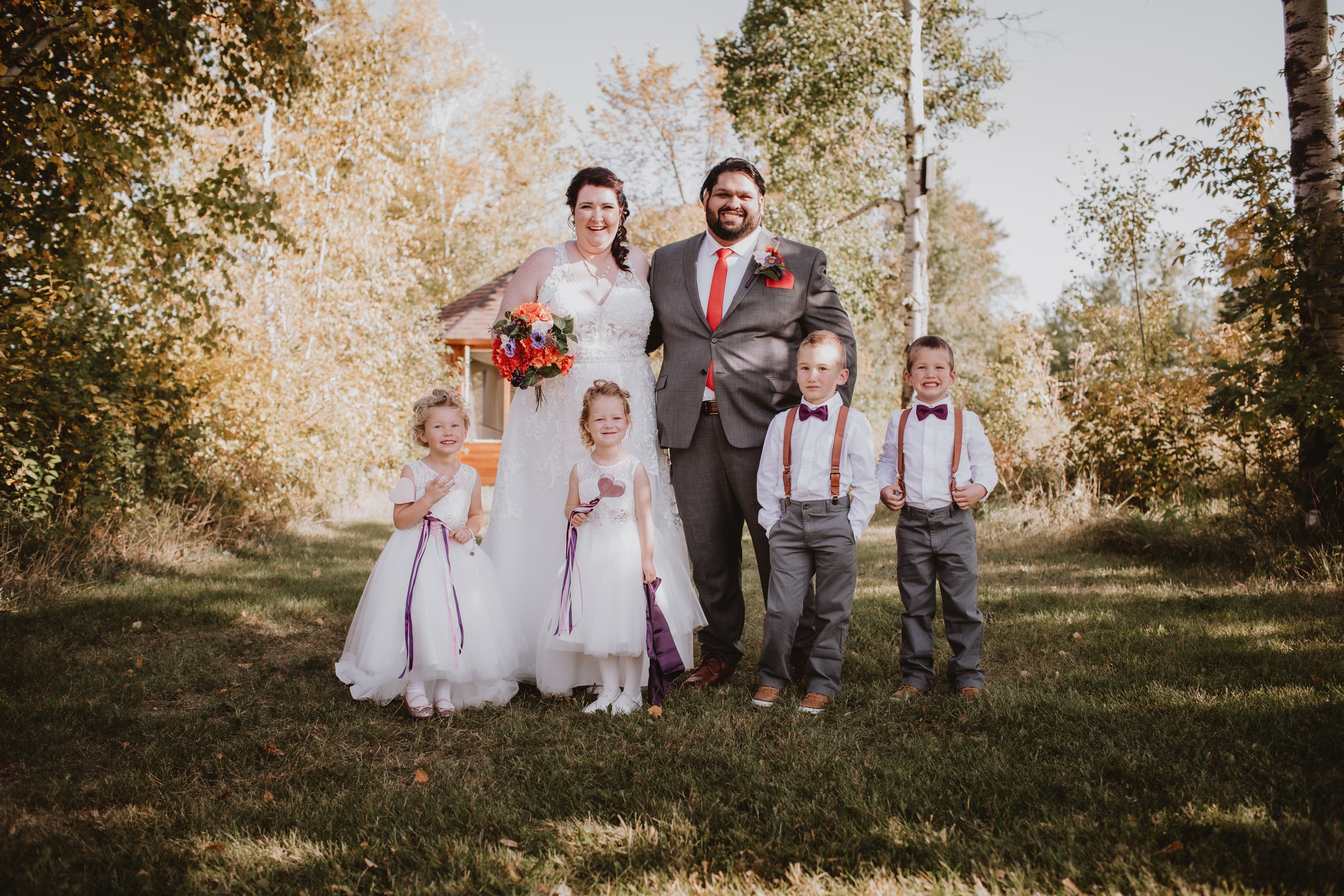 Flower girls and ring bearers pose with wedding couple.