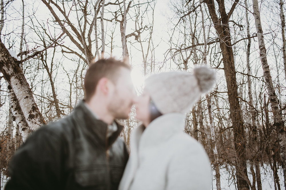 Engaged couple in near kiss, blurred with forest and sun in background in focus.