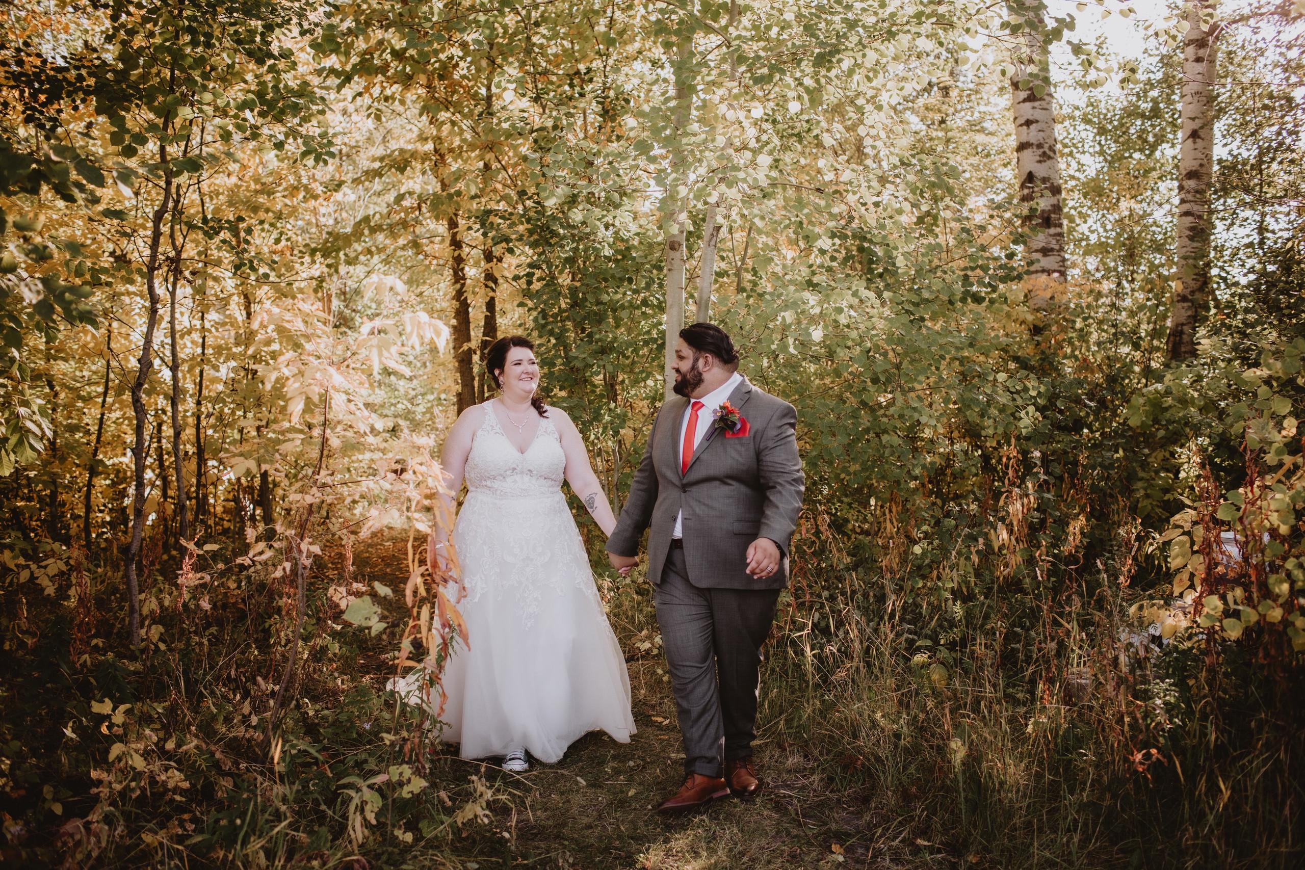 Manitoba Wedding Couple walks through forest during golden hour wedding photos.