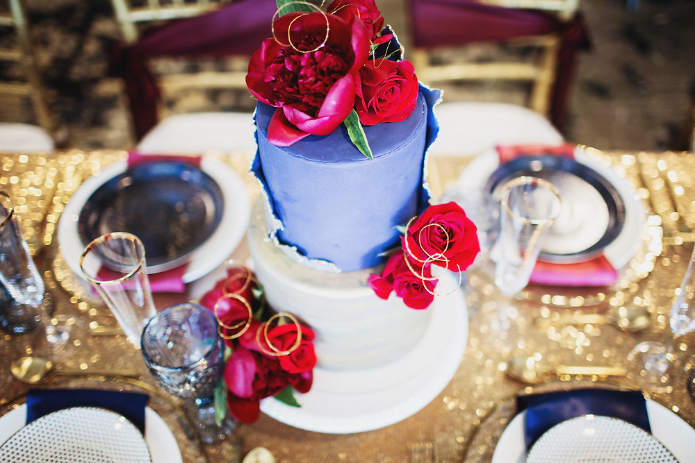 Marvel themed wedding cake in blue and gold with red flowers, created by Roll Cake Bakery in Winnipeg, Manitoba.