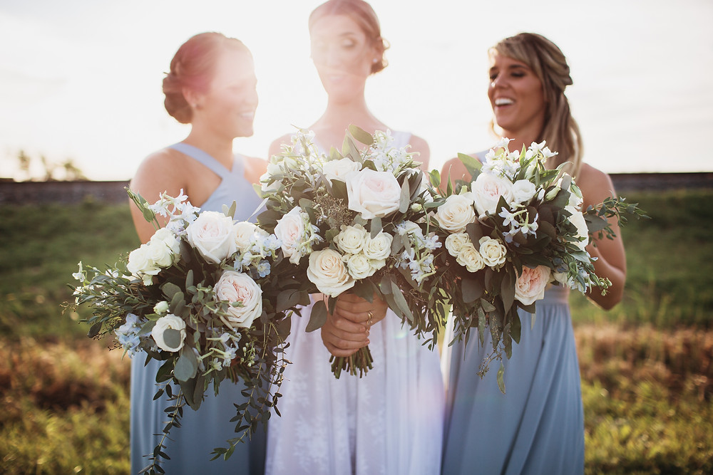 Bride and bridesmaids pose with wedding bouquets during sunset photos for fall wedding day.