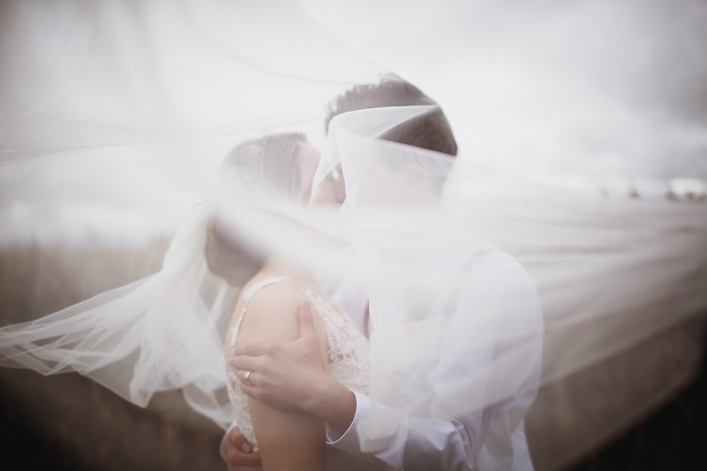 Veil sweeps over bride and groom as they kiss right after their wedding ceremony in Manitoba.