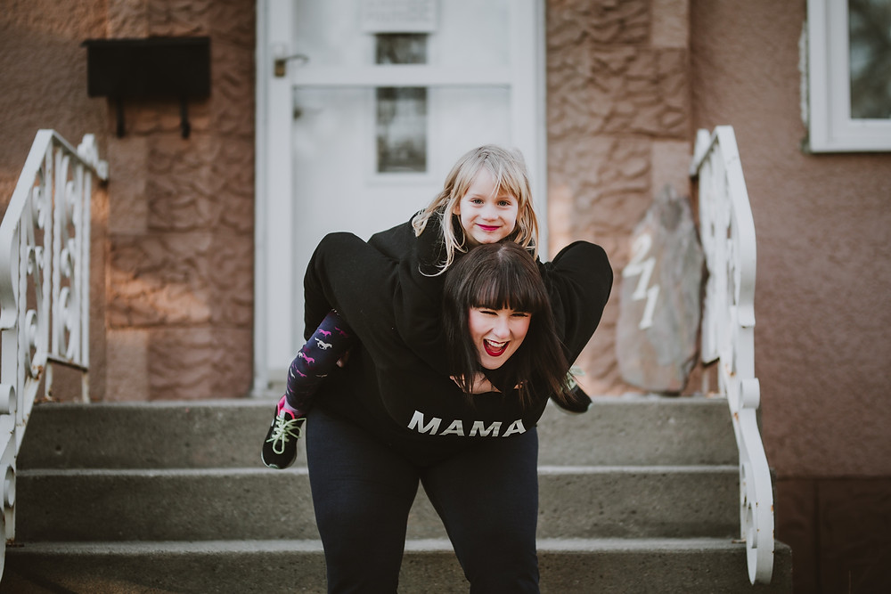 Mom gives daughter a piggyback ride during photo session.