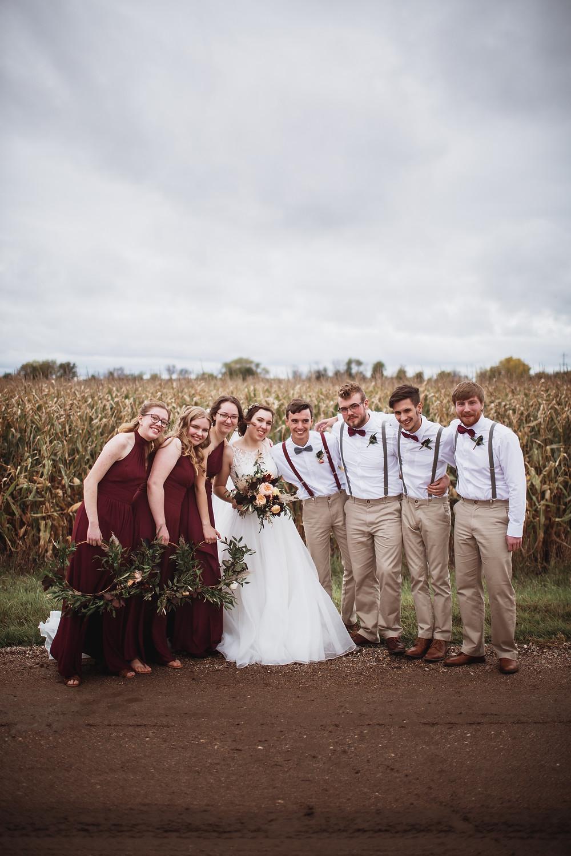Burgundy bridesmaid dresses, groomsmen in khaki trousers and suspenders.a