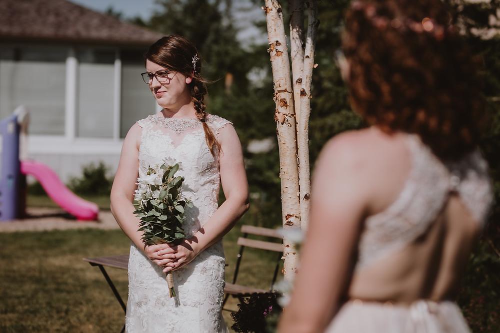 Brides standing under birch arch from House of Silk.